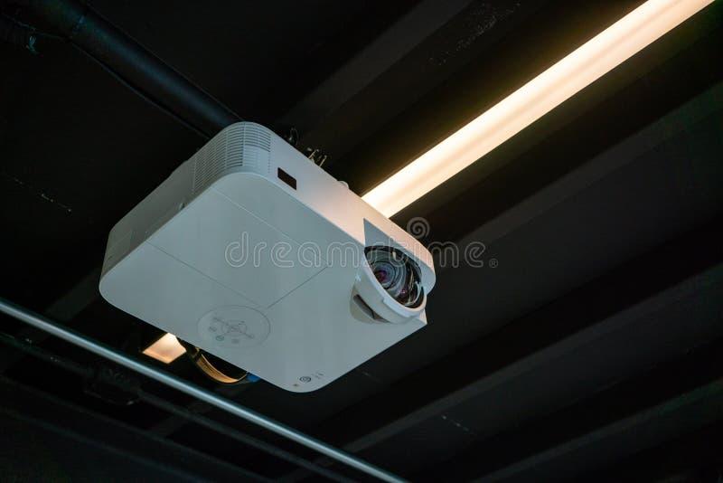 Hängande vit projektor för svart tak mot svart bakgrund royaltyfria foton