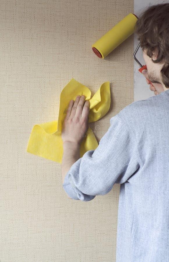 hängande wallpaperarbetare arkivbilder