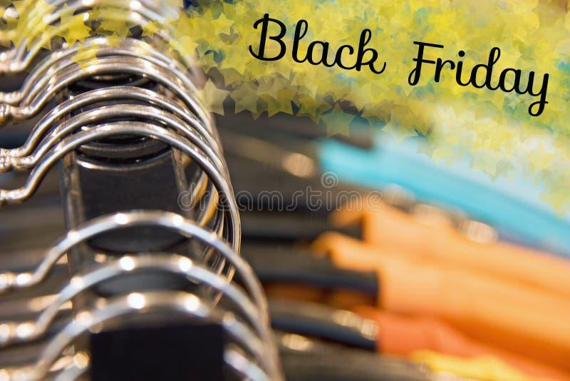 Hängare i en shoppa med färgrik kläder Svart fredag begrepp arkivbilder
