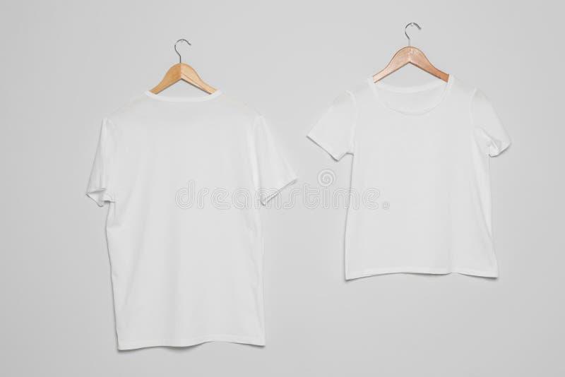 Hängare med tomma t-skjortor på grå bakgrund arkivfoton