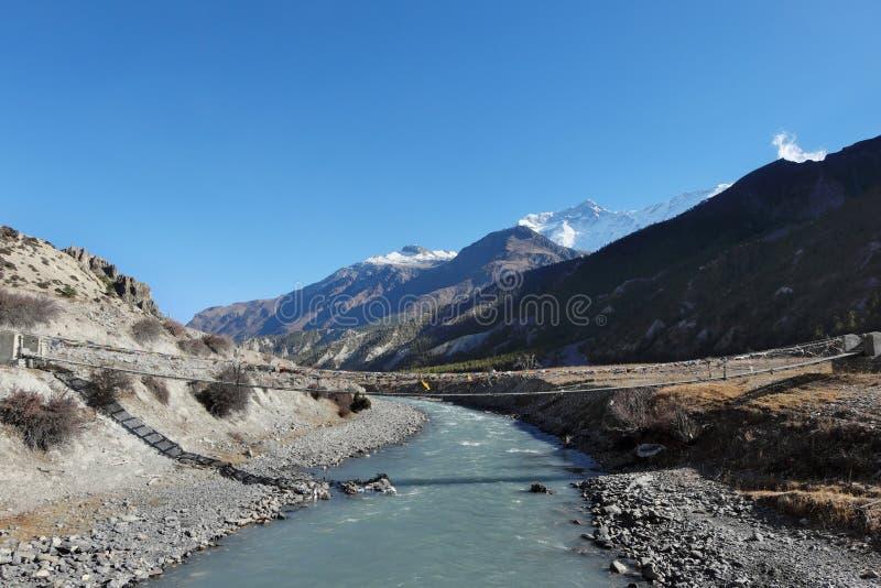 Hängebrücke über dem Fluss im nepalesischen Himalaja stockfotografie