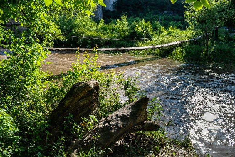 Hängebrücke über einem turbulenten Fluss, der Sonnenlicht reflektiert lizenzfreie stockbilder