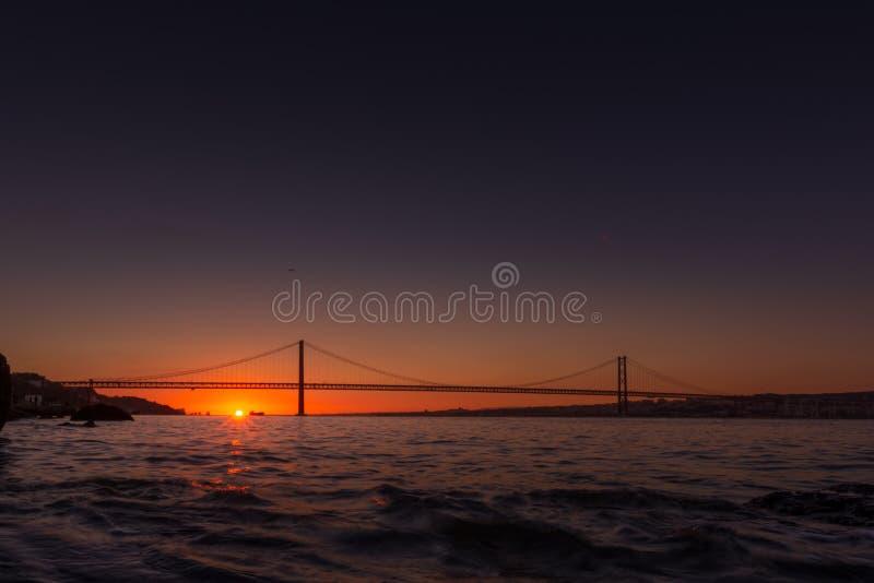 Hängebrücke über Fluss in Lissabon bei Sonnenuntergang stockfoto