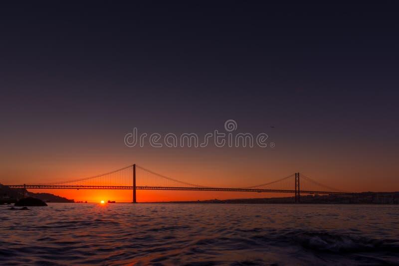 Hängebrücke über Fluss in Lissabon bei Sonnenuntergang lizenzfreie stockfotografie