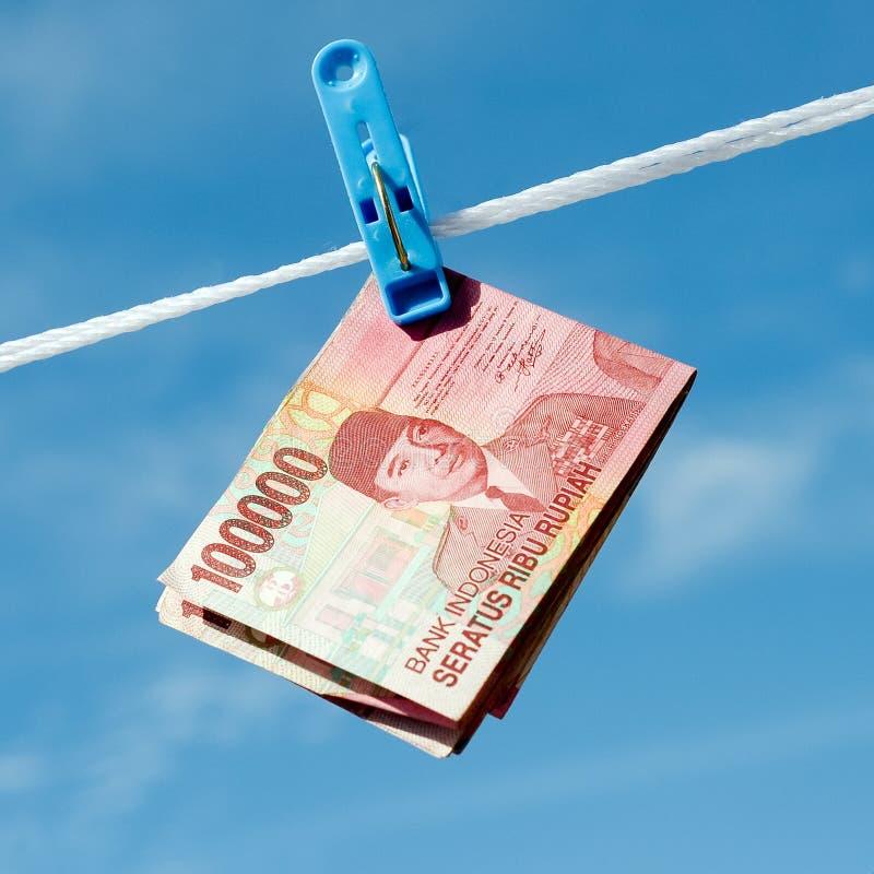 Hängen an der indonesischen Banknotenrupie des Seils lizenzfreies stockbild