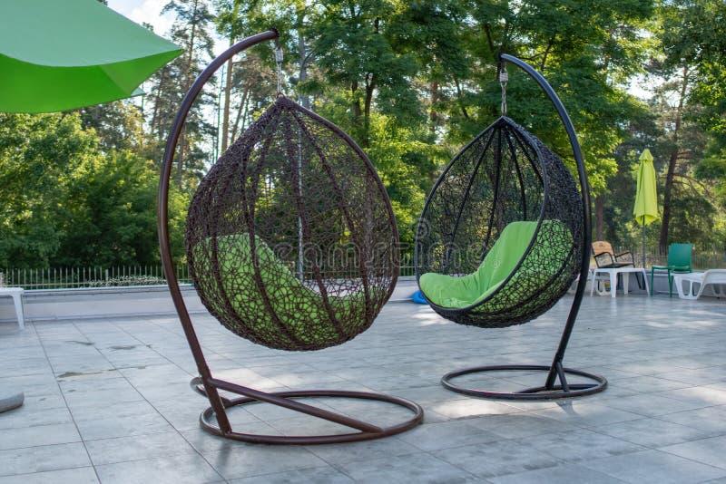 Hängende geflochtene Stühle in der Erholungsstätte im Sommer Konzept der Erholung und der Freizeit draußen Luxus-Resort stockfotos