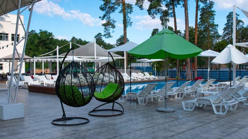 Hängende geflochtene Stühle und Swimmingpool und Sonnenschirme in der Erholungsstätte im Sommer Konzept der Erholung und stockfotos
