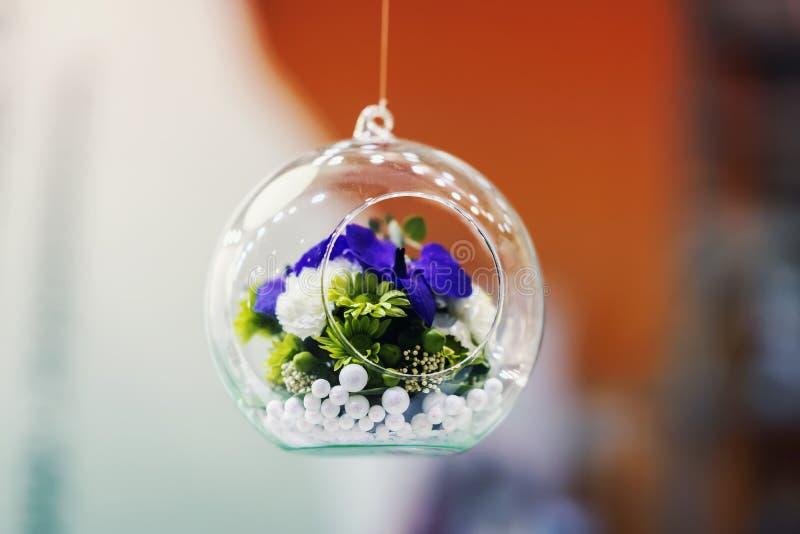Hängende Glaskugel, Blase mit bunten Blumen nach innen, heller weißer und roter Hintergrund, Dekoration, stilvolles floristry stockbilder