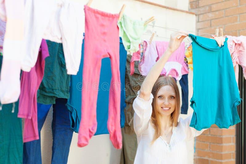 Hängende Kleidung des Mädchens zu trocknen stockfoto