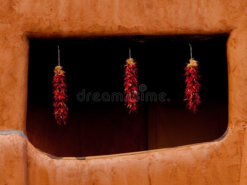 Hängende ristras Santa Fe New Mexicps im Fenster des luftgetrockneten Ziegelsteines stockfotografie