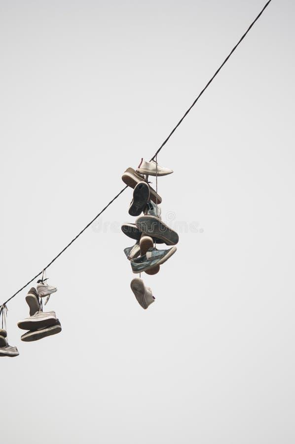 Hängende Schuhe von einem Draht lizenzfreie stockbilder