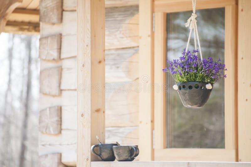 Hängender Pflanzer der einzigartigen handgemachten schwarzen Tonwaren mit schönen Glockenblumen und zwei Kaffeetassen stockbild