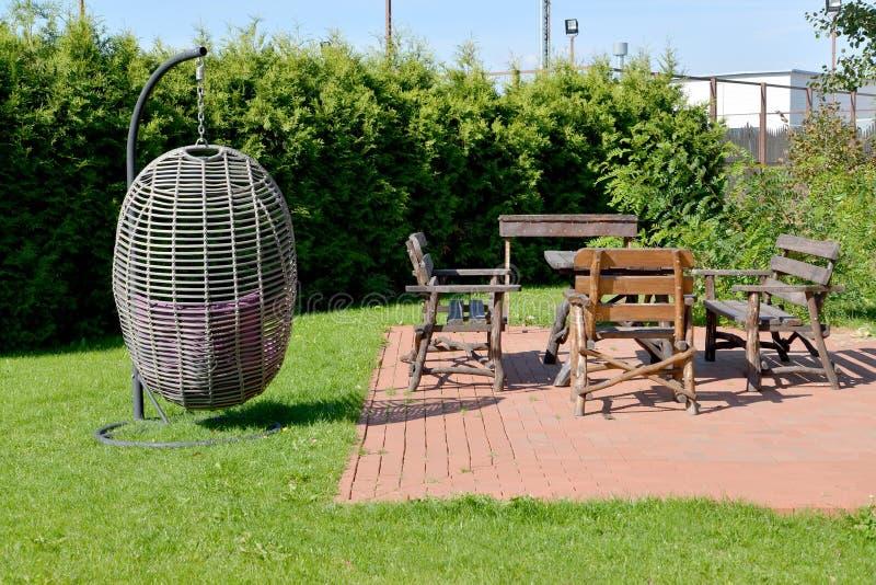 Hängender Stuhl und hölzerne Gartenmöbel im Gebiet von Th stockbild
