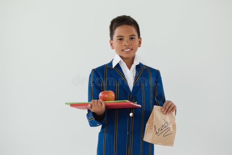 Hänger löst det hållande äpplet för skolpojken, böcker och disponibel lunch mot vit bakgrund fotografering för bildbyråer