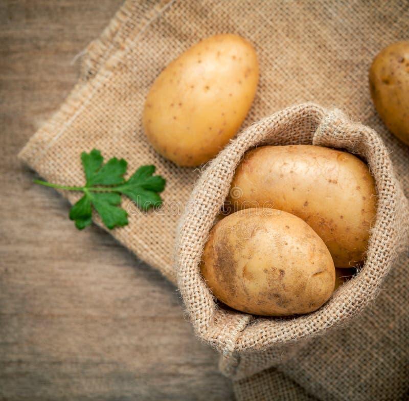 Hänger löst nya organiska potatisar för Closeup i hampaskull med persilja på royaltyfri foto