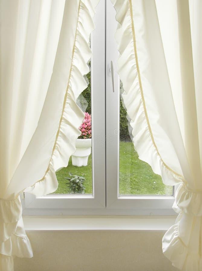 hänger upp gardiner det vita fönstret fotografering för bildbyråer