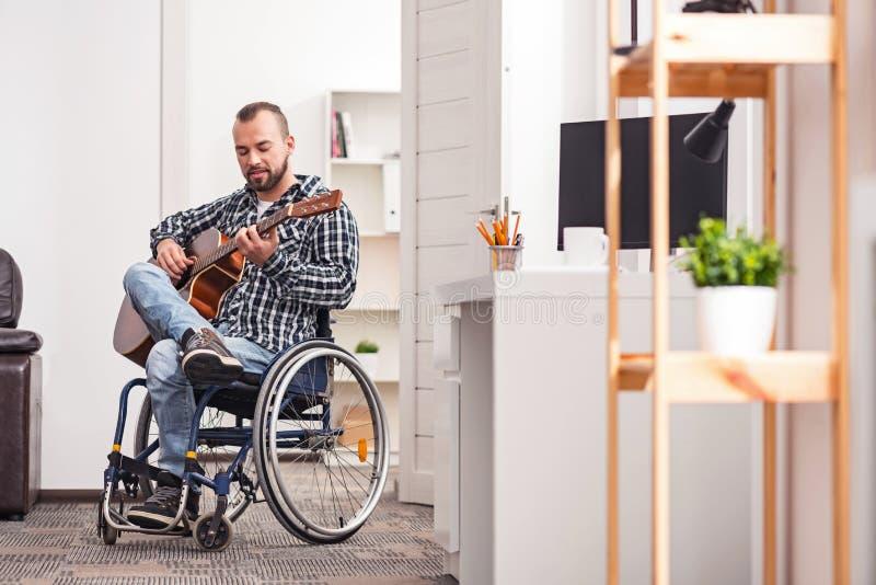 Hängiven handikappad man som spelar musikinstrumentet arkivfoton