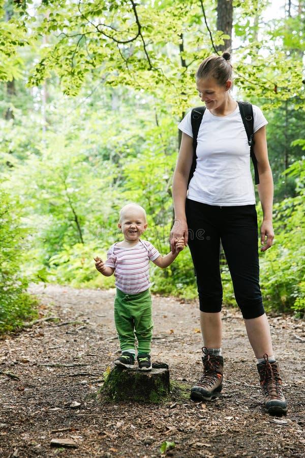 Hängiven moder som rymmer händer med hennes son som går i träna royaltyfri bild