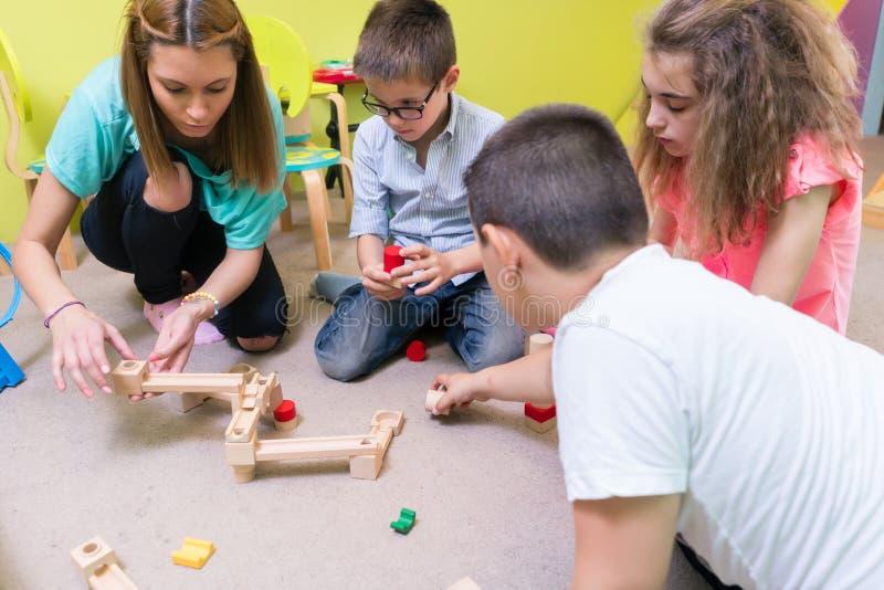 Hängivna barn för portion för dagislärare med konstruktion royaltyfri bild