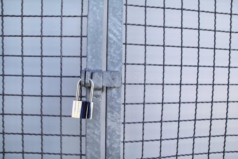 Hänglåset på ett chainlinkstaket/en huvudnyckel och en gammal rostig kedja med stålburen, slut upp/stängde låset med kedjan på me royaltyfri fotografi