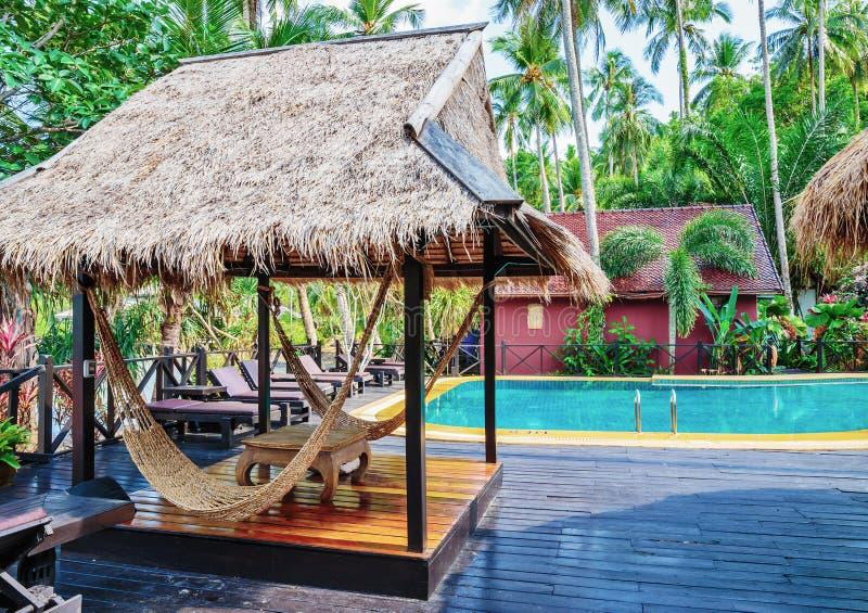 Hängmatta under parasollen i tropisk trädgård arkivfoto