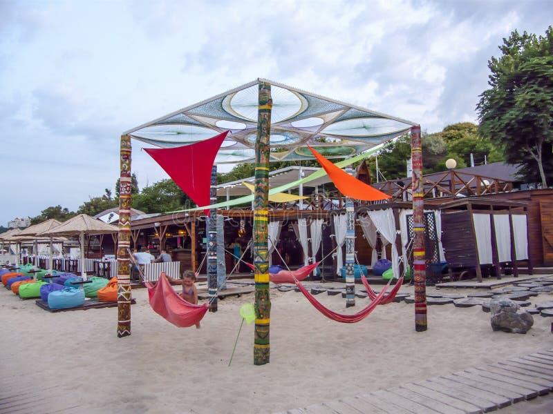 Hängmattagunga på träetniska kolonner, vide- mandalas för rep, mång--färgade trådar, afton Odessa, Ukraina för strandsemestersomm royaltyfri foto