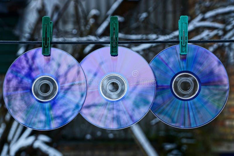 Hängning för tre CD-SKIVOR på en tråd på klädnypor arkivbild