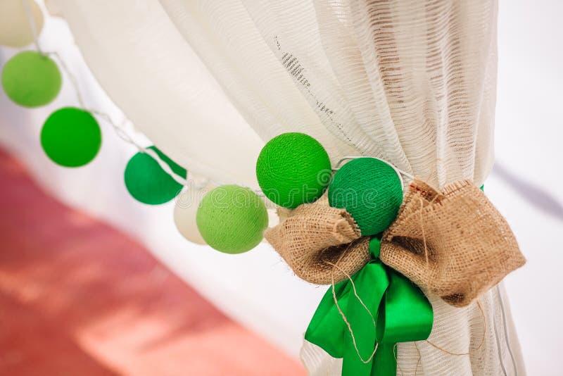 Hängningar för girland för bomullsbollar på en vit gardin Ljus kulör garnering bröllop arkivbild