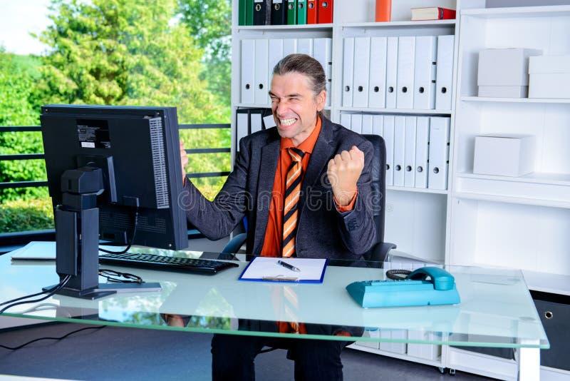 Häpen affärsman på hans skrivbord royaltyfri foto