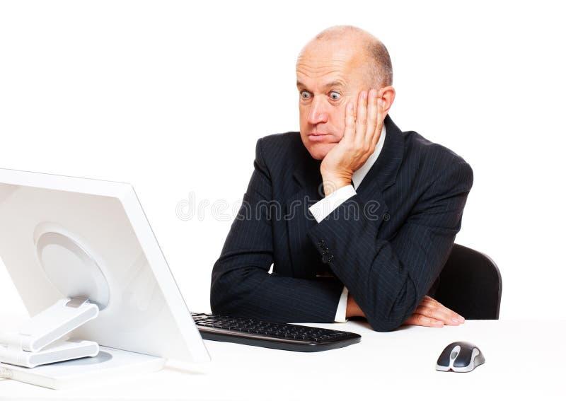 häpen affärsman som ser bildskärmen royaltyfria foton