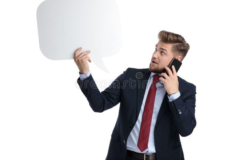 Häpen affärsman som ser till en tom anförandebubbla royaltyfria foton