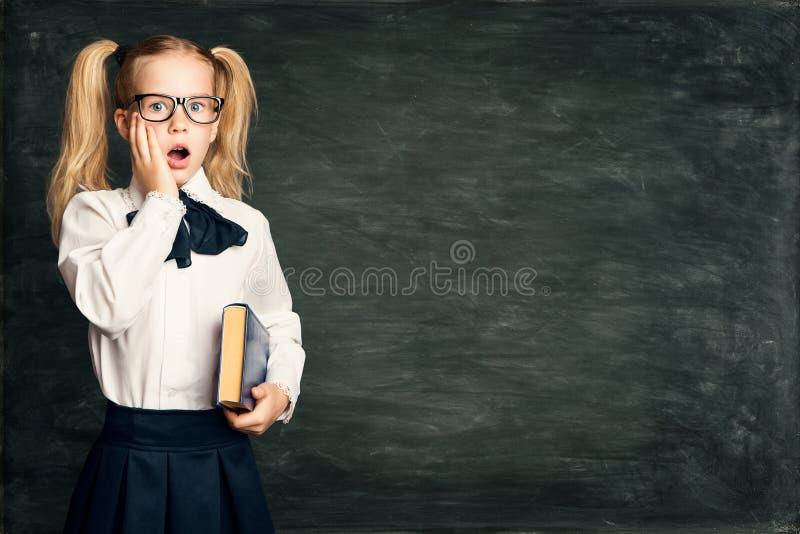 Häpen barnflicka på skolasvart tavlabakgrund, förvånad unge över svart kritabräde arkivbild