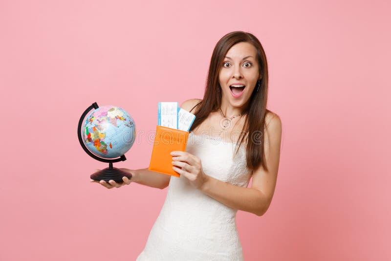 Häpen brudkvinna i det vita jordklotet för bröllopsklänninginnehavvärld, biljett för passlogipasserande som utomlands går för brö royaltyfria foton