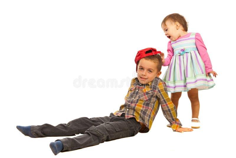 Häpen Flicka Om Pojkehatten Royaltyfri Foto