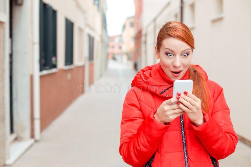 Häpen kvinna som mottar chockerande nyheterna på en smart telefon på stren arkivbilder