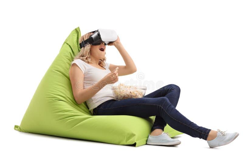 Häpen kvinna som placeras på en sittkudde genom att använda en VR-hörlurar med mikrofon royaltyfri fotografi