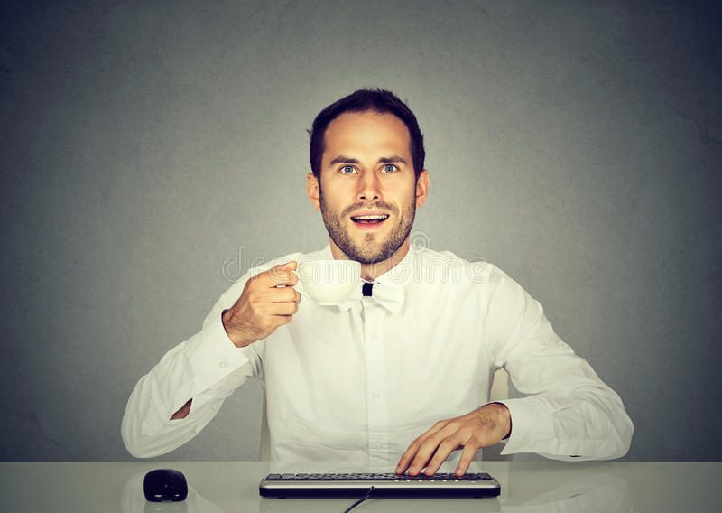 Häpen man som använder den hållande koppen kaffe för dator royaltyfri fotografi