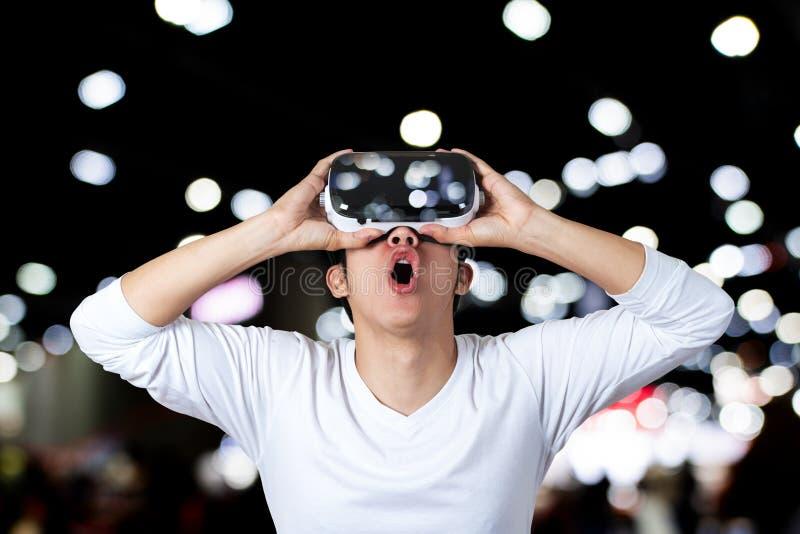 Häpen man som ser till och med VR-skyddsglasögon royaltyfri foto