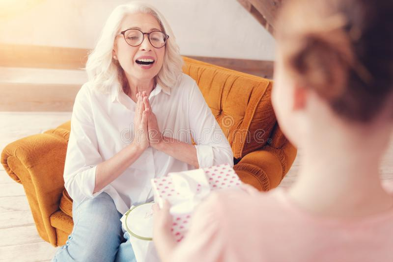 Häpen pensionerad dam som får emotionell, medan motta gåvan royaltyfri fotografi