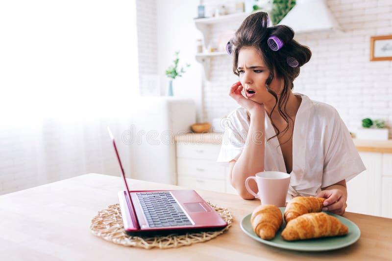 Häpen undrad blick för ung kvinna på bärbara datorn Hållande ögonen på film i kök Giffel och kopp av drinken på tabellen of?rsikt royaltyfria foton