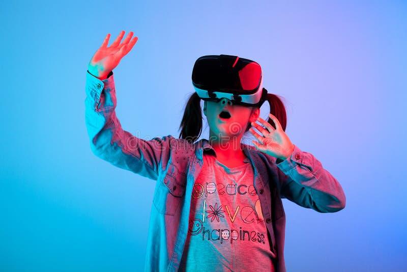 Häpen ung flicka som erfar virtuell verklighet fotografering för bildbyråer