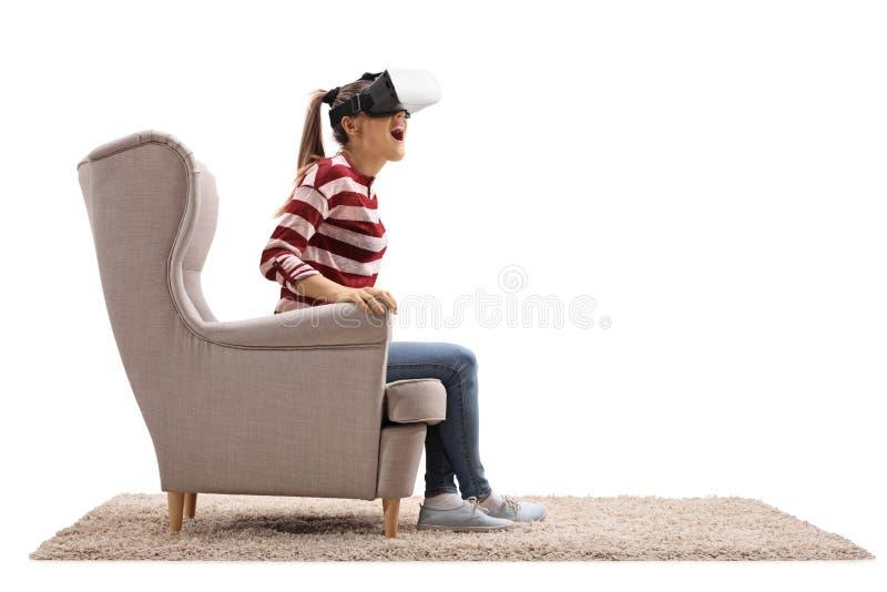 Häpen ung kvinna som placeras i en fåtölj genom att använda en virtuell verklighet royaltyfri foto