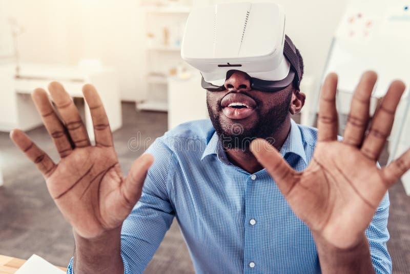 Häpen ung man som tycker om virtuell verklighetexponeringsglas royaltyfri bild