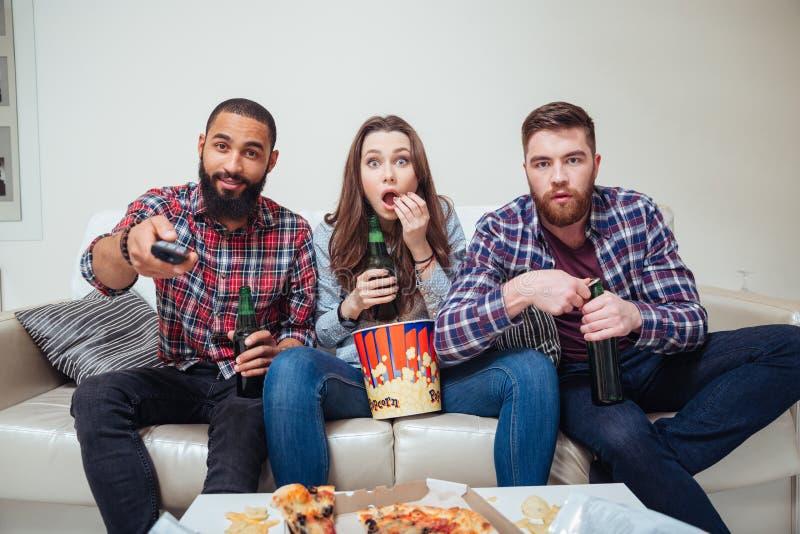 Häpna chockade vänner som håller ögonen på tv och äter popcorn på soffan royaltyfria foton