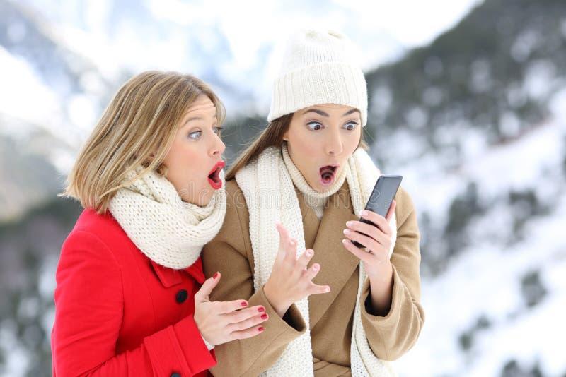 Häpna vänner med en smart telefon i vinter arkivbild