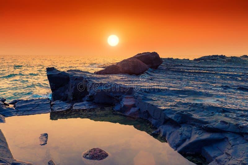 Härdad lava och hav på solnedgången arkivbild
