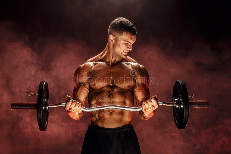 Härdad man som gör övning med den tunga stången royaltyfri foto