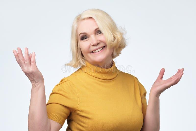Härlig äldre kvinna i gult le för tröja royaltyfria foton