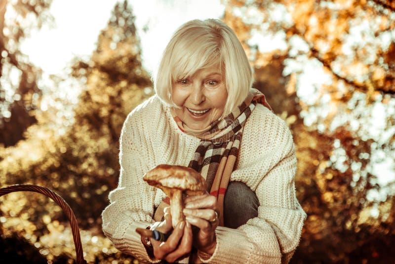 Härlig äldre kvinna som förvånas finna en champinjon arkivbilder
