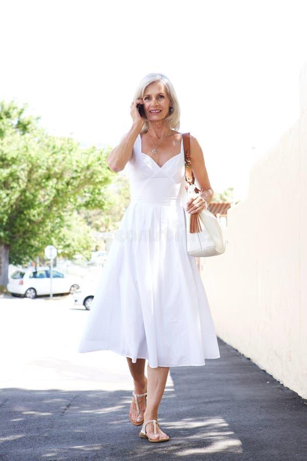 Härlig äldre kvinna som går på trottoaren på telefonen arkivfoton